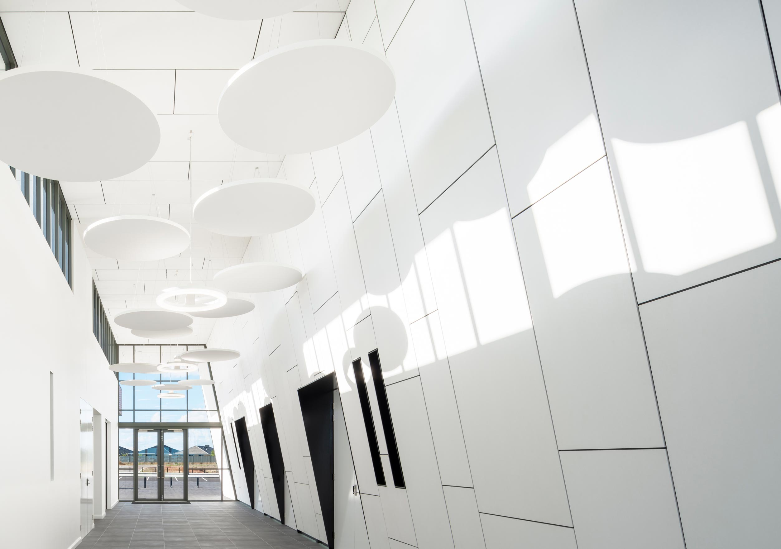 White cladded internal hallway of Rossiter Sporting Pavilion with white circular hanging pendant lights