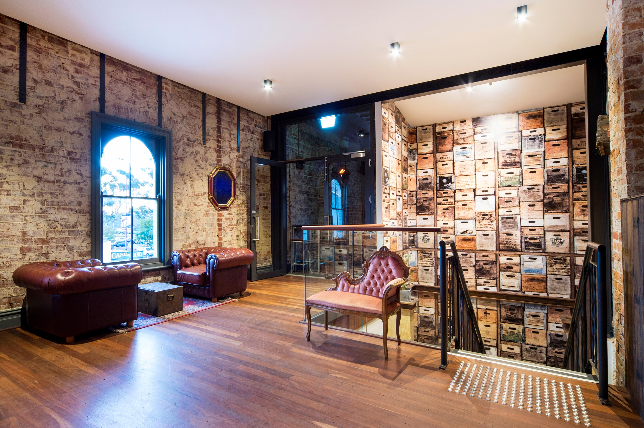 Wallpapered stairwell with leather and velvet lounges on first floor landing of the Guildford Hotel