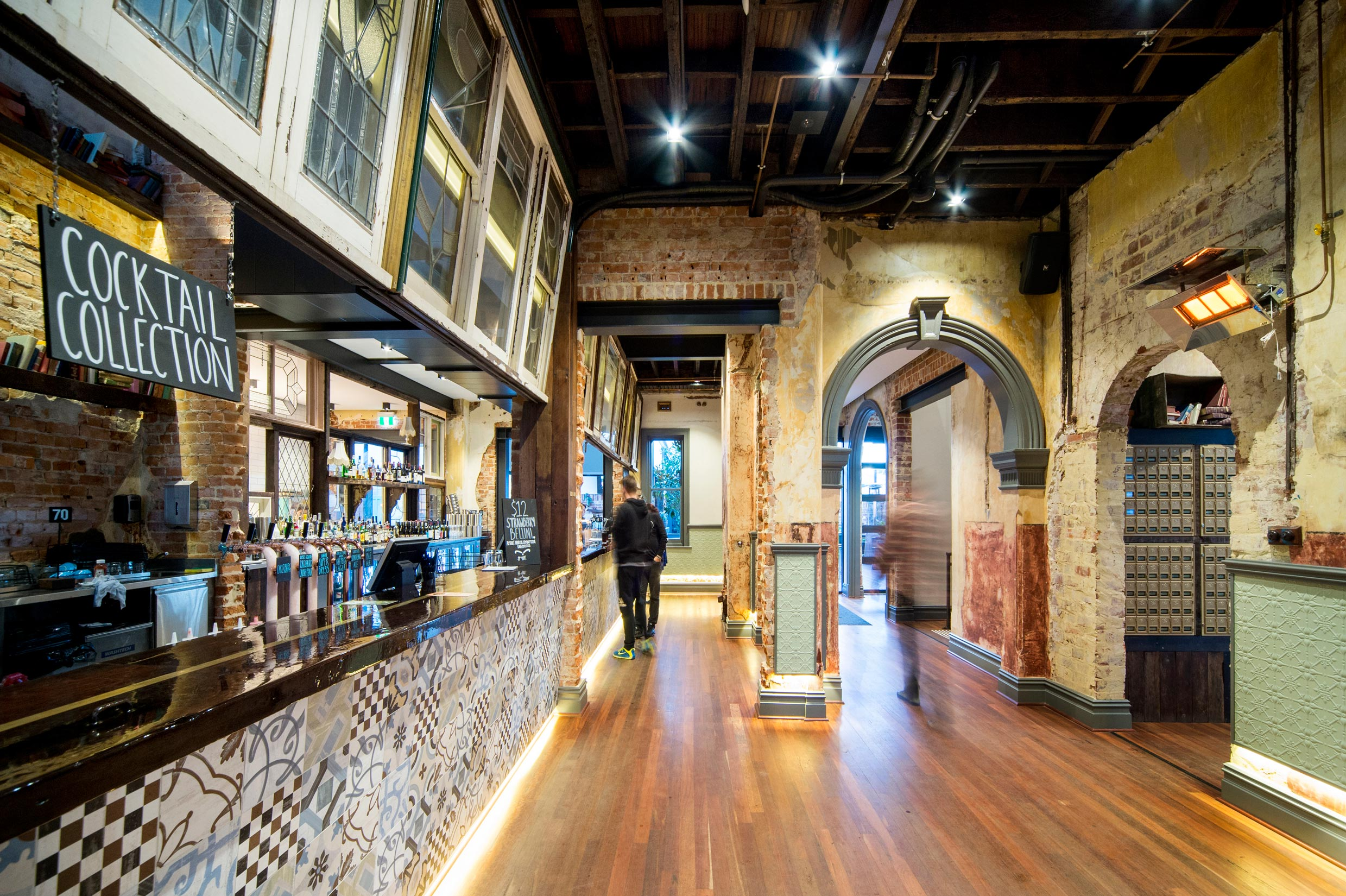 Heritage style bar at the Guildford Hotel with timber floors, tiled bar, exposed brick walls and original archways.