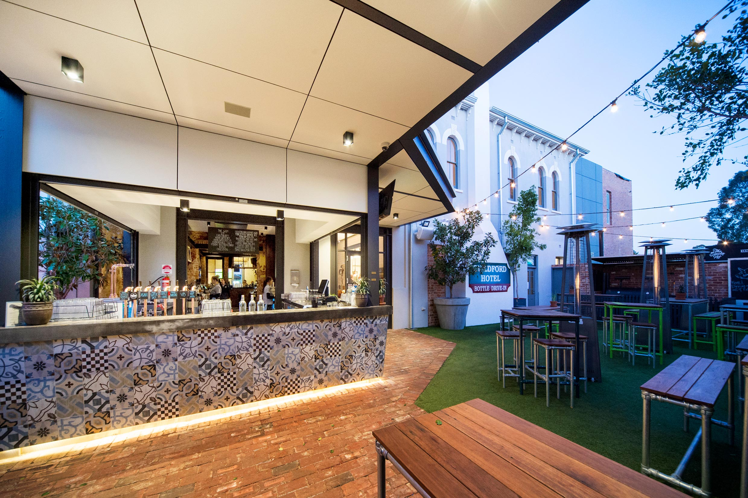 Beer garden outdoor bar with grass and fairy lights at the Guildford Hotel