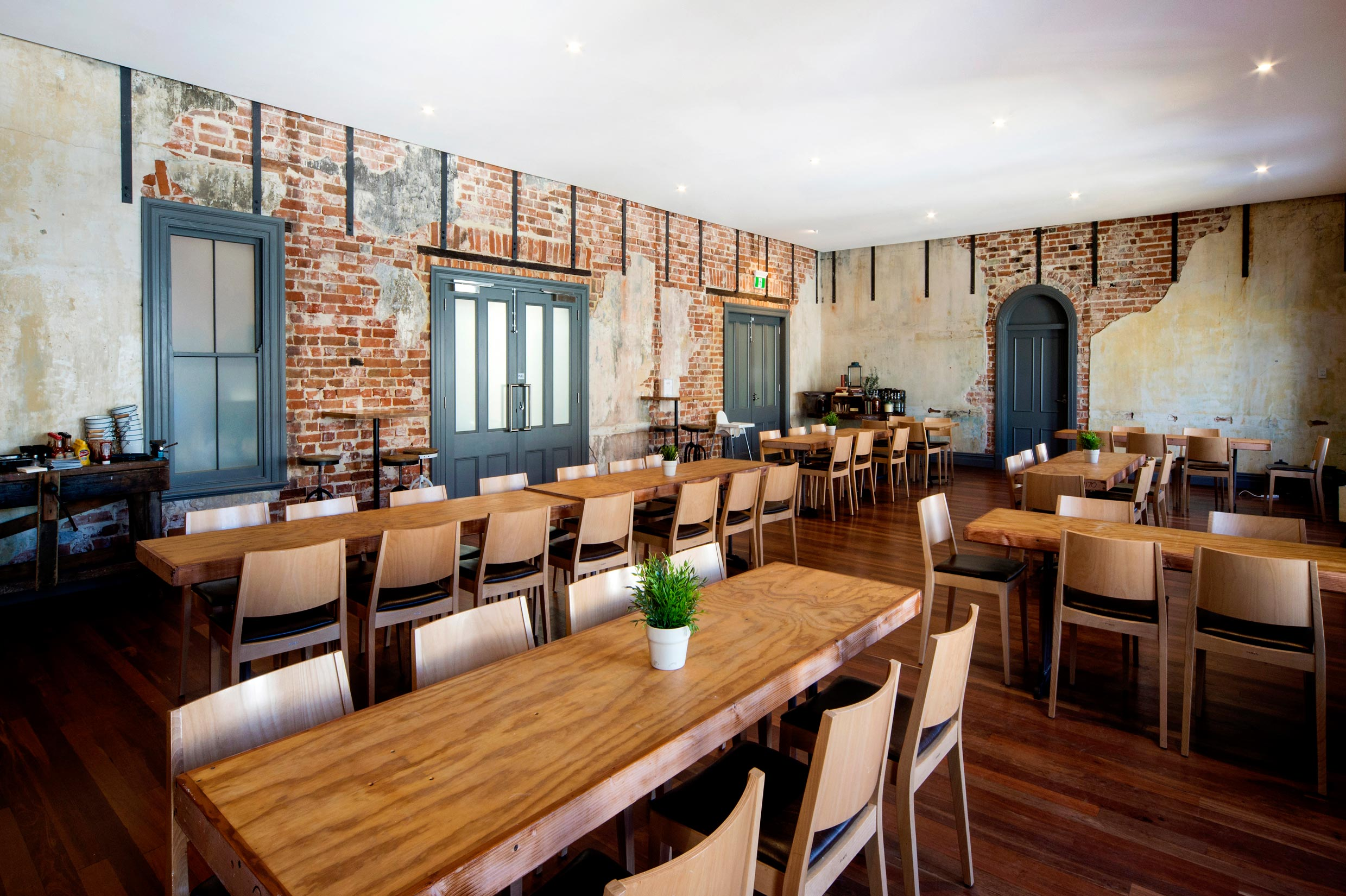 The Guildford Hotel heritage function room with dining tables, and exposed restored brick walls