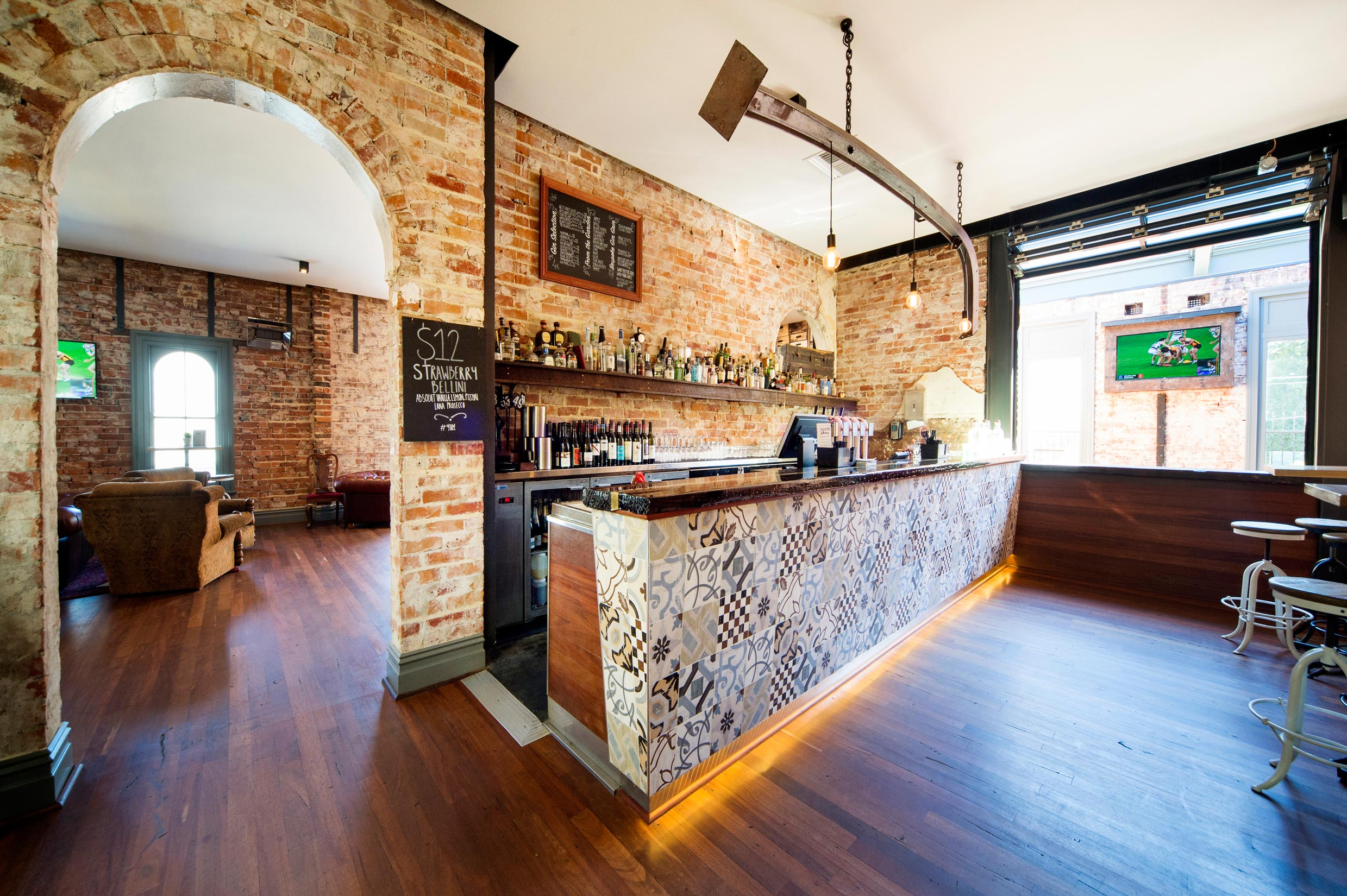 Upstairs bar at the Guildford Hotel with restored brick walls, coloured tiles on the bar, and suspended steel beam