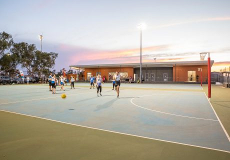 Outdoor netball courts with Faye Gladstone Netball Pavilion behind in Port Hedland