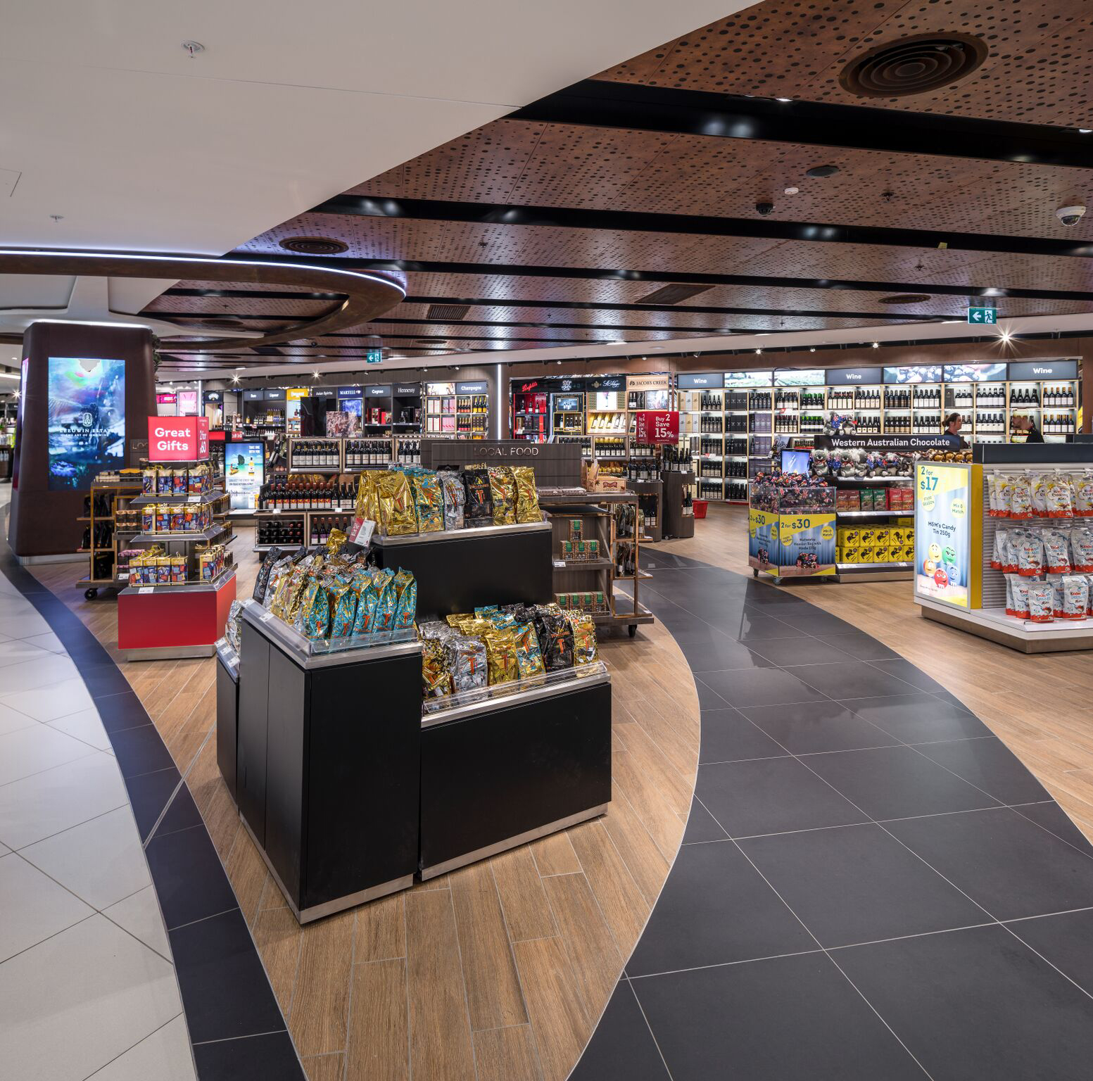 Duty Free retail kiosks at the Perth International Airport with dark organic shapes on floor and ceiling