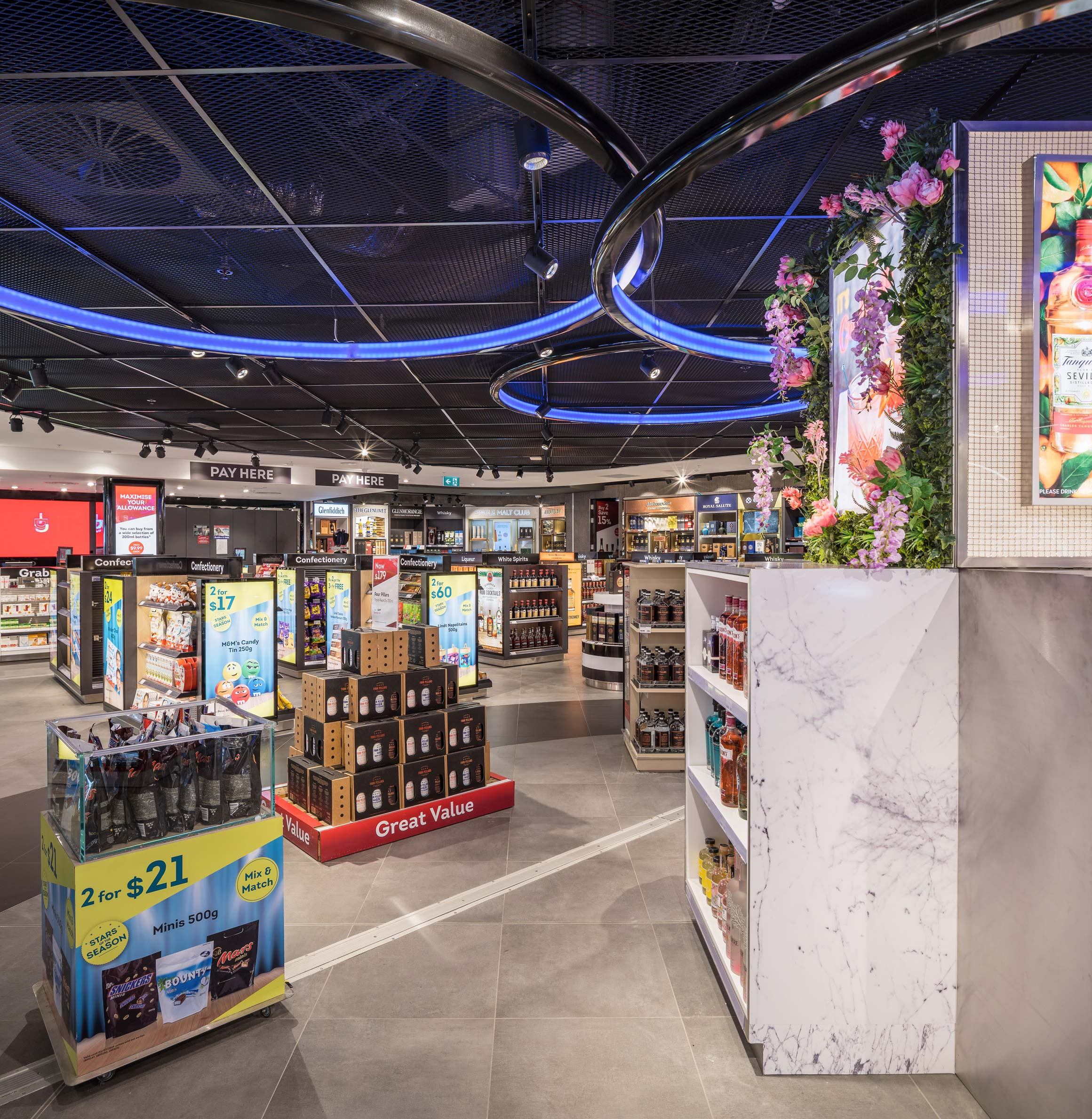 Liquor retail stands at Perth International Airport Duty Free with huge circular blue ceiling lights