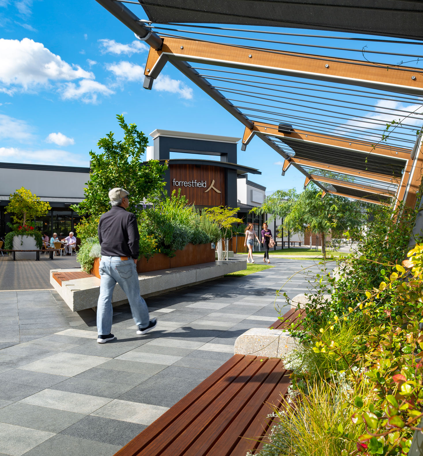 footpath to the entrance of Forrestfield Forum Shopping Centre surrounded by planter boxes and timber seating
