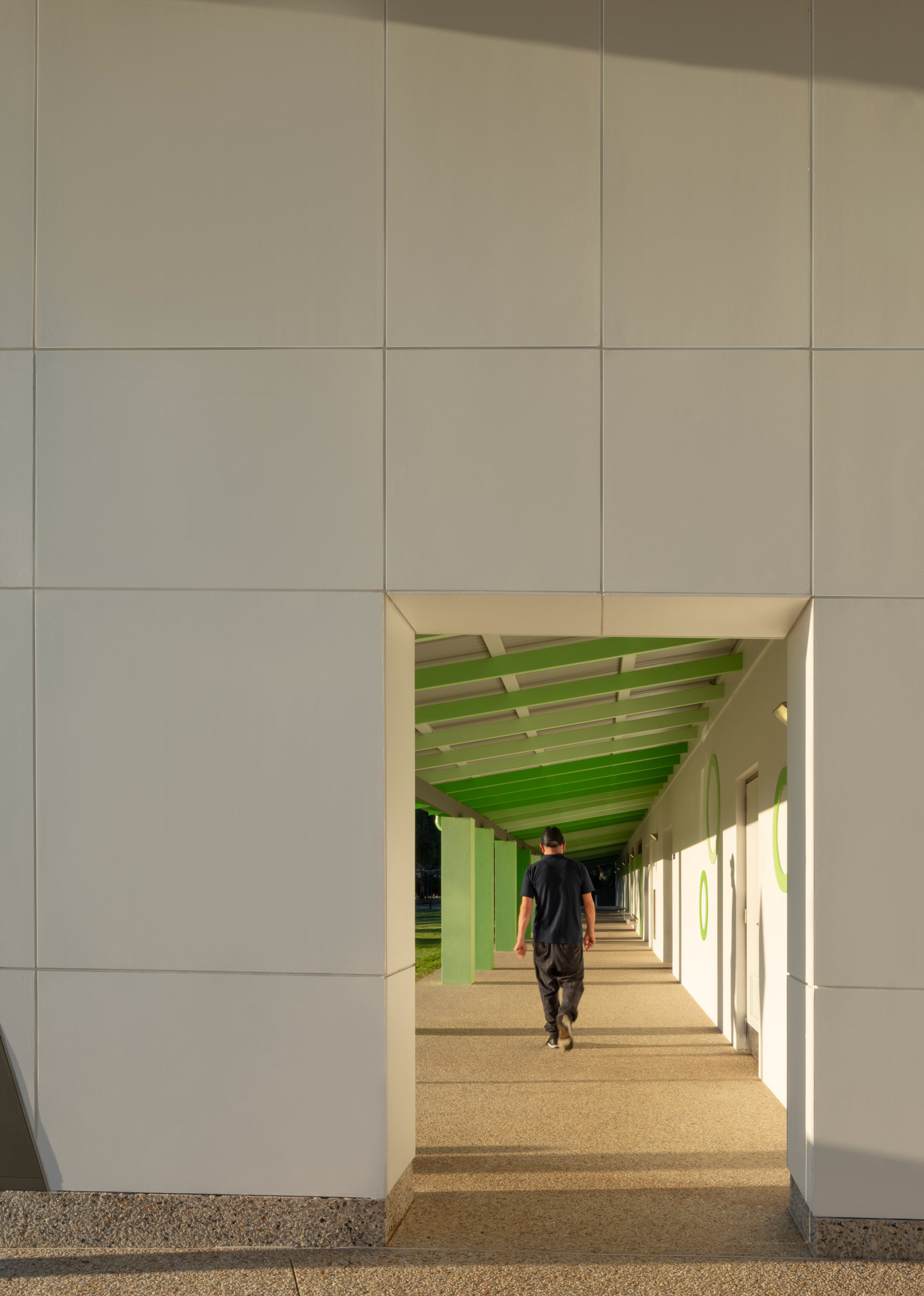 Carine Hall Rec Centre view through wall cutout down outdoor walkway with green beams