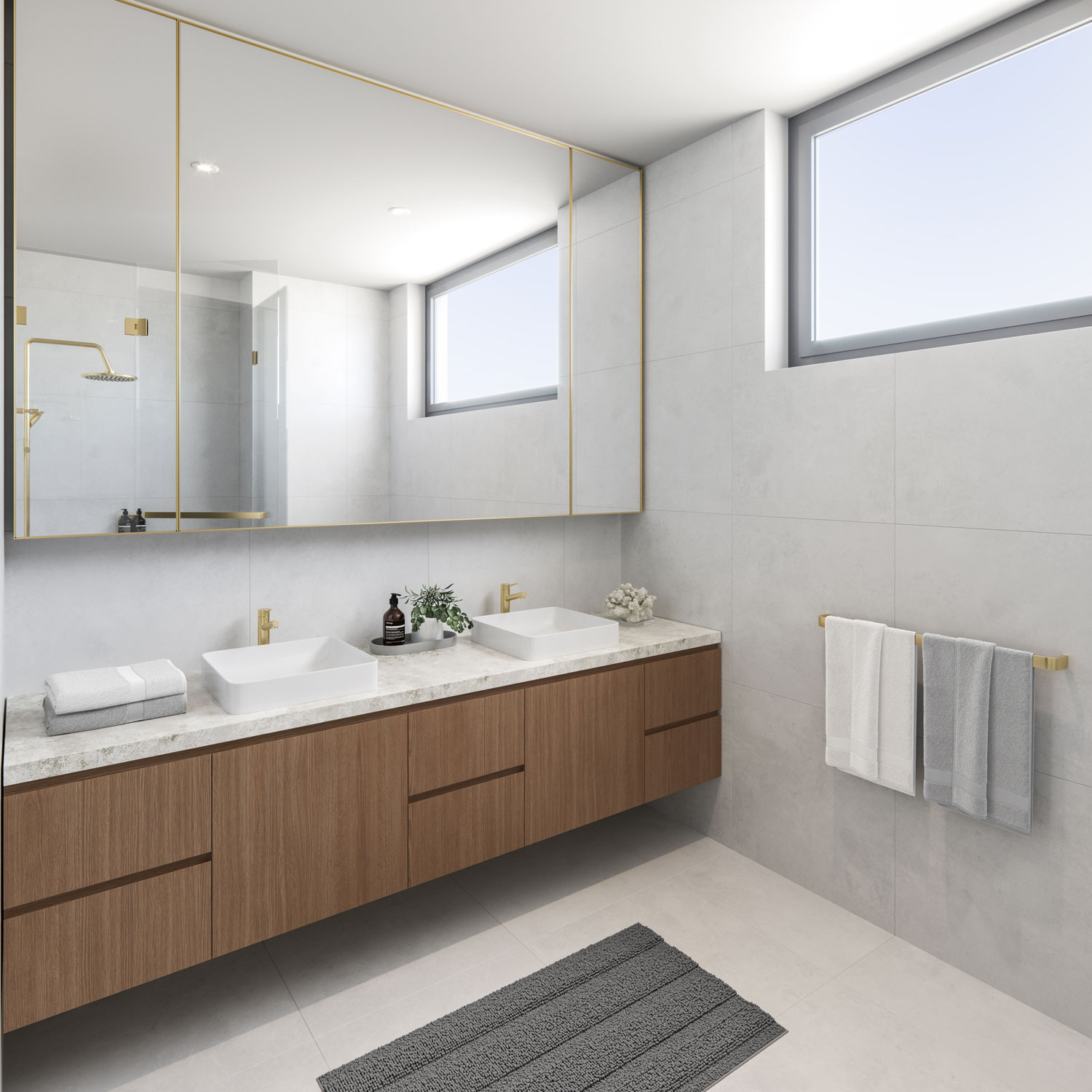 Light grey tiled bathroom, with timber under sink cabinetry, brass tapware fixtures and marble benchtop in Elizabeth Residences Cottesloe Apartments