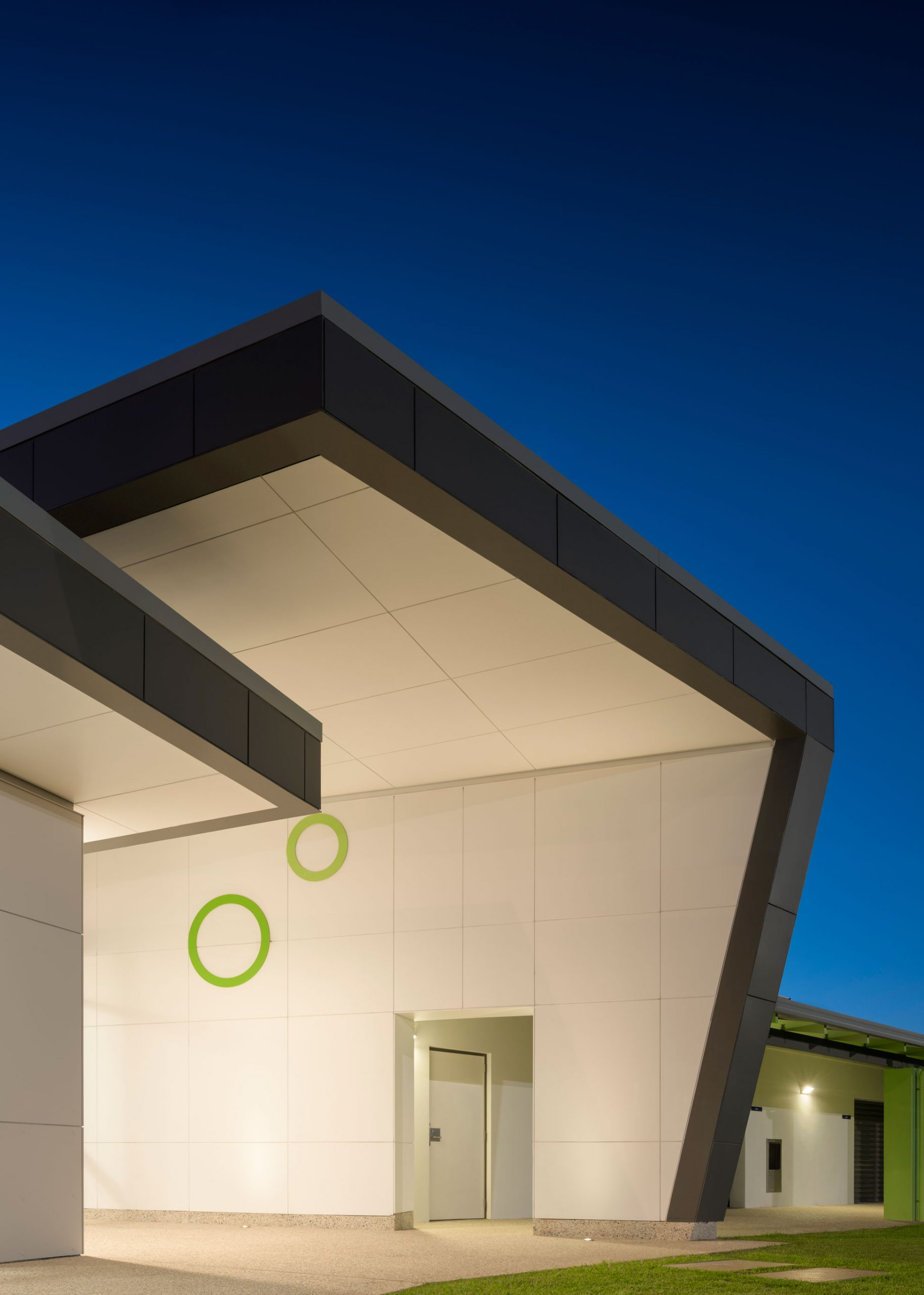 Carine Hall Rec Centre entrance lit up at night, with white angled walls with green circles and grey angled roof